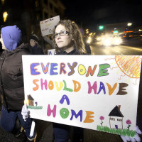 "April Chapman of Lewiston carries a sign that reads, ""Everyone Should Have a Home,"" during the Lewiston-Auburn Homeless Vigil in Lewiston on Wednesday. About 100 people marked National Homeless Persons' Memorial Day by walking from the Trinity Episcopal Church to the Calvary United Methodist Church by candlelight. The annual event was held on the winter solstice, the shortest day and longest night of the year. New Beginnings and the Lewiston/Auburn Alliance for Services to the Homeless hosted the event. Chapman walked with a large group from Common Ties Mental Health Services."