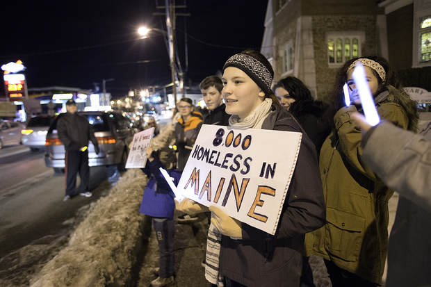 """Aura Foster, 16, of Poland holds a sign that reads, """"8,000 Homeless in Maine,"""" during the Lewiston-Auburn Homeless Vigil in Lewiston on Wednesday."""