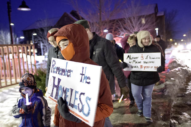 "Emerson Spencer-Reed, 10, of New Gloucester carries a sign that reads, ""Remember the Homeless,"" during the Lewiston-Auburn Homeless Vigil in Lewiston on Wednesday."