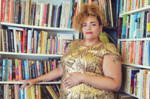 Bianca is a tall fat light skinned disabled queer AfraLatina who is in a gold dress with gold beaded geometric designs with a smile on her face and looking at the camera. Her hair is up and her blondish brown curls cascade around her head. She has on red lipstick and large round gold earrings. She stands in front of a full bookcase.